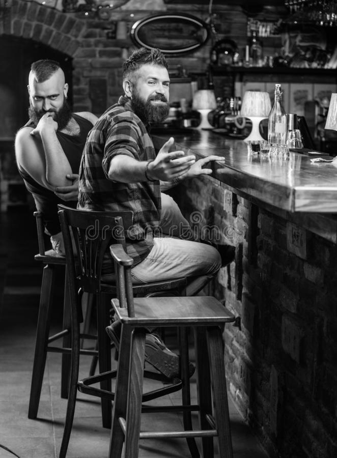 Hipster brutal bearded man spend leisure with friend at bar counter. Men relaxing at bar. Friday relaxation in bar. Friendship and leisure. Friends relaxing in stock image