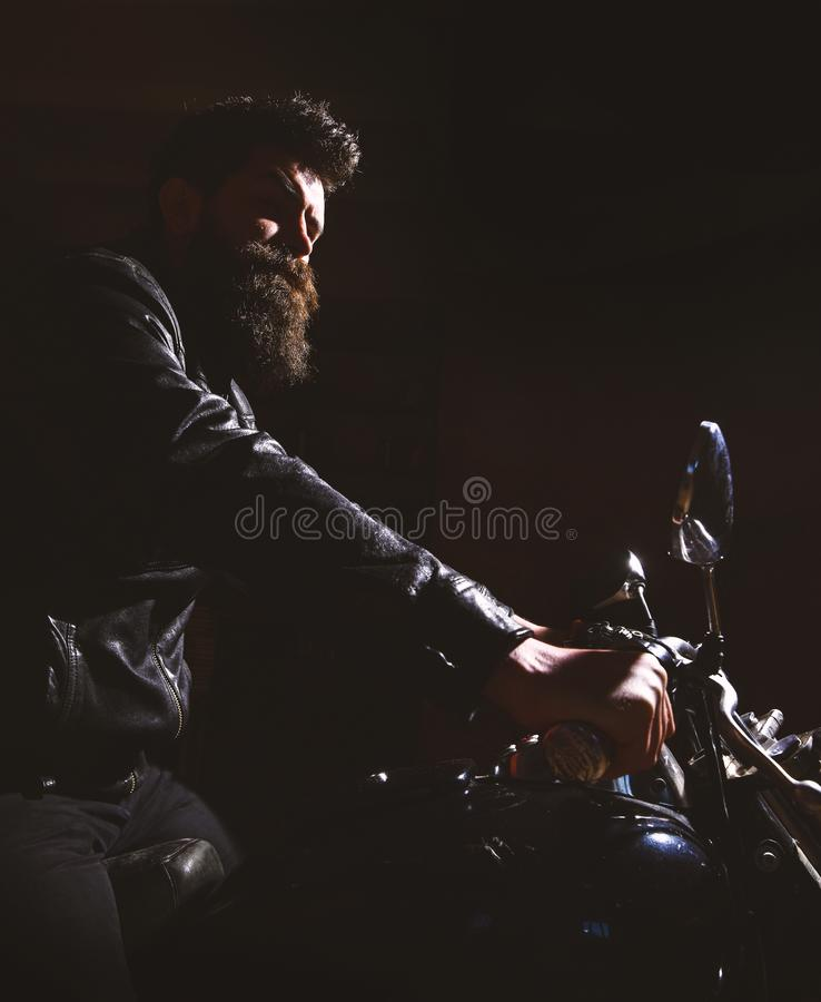 Hipster, brutal biker in leather jacket riding motorcycle at night time, copy space. Man with beard, biker in leather. Jacket sitting on motor bike in darkness stock photo