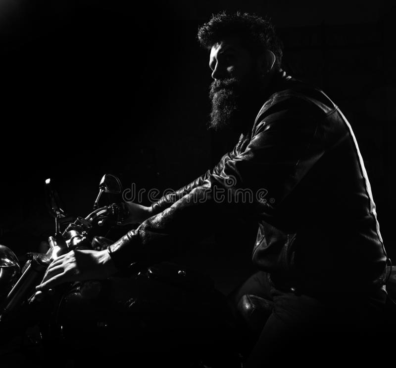 Hipster, brutal biker in leather jacket riding motorcycle at night time, copy space. Night rider concept. Man with beard. Biker in leather jacket sitting on royalty free stock photography