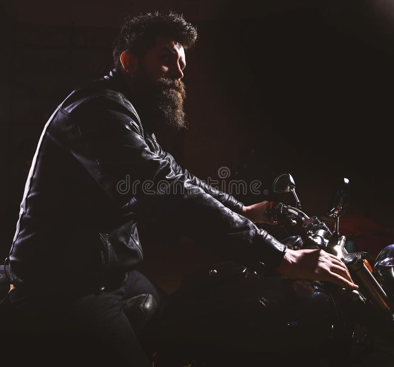 Hipster, brutal biker in leather jacket riding motorcycle at night time, copy space. Night rider concept. Man with beard. Hipster, brutal biker in leather jacket stock image