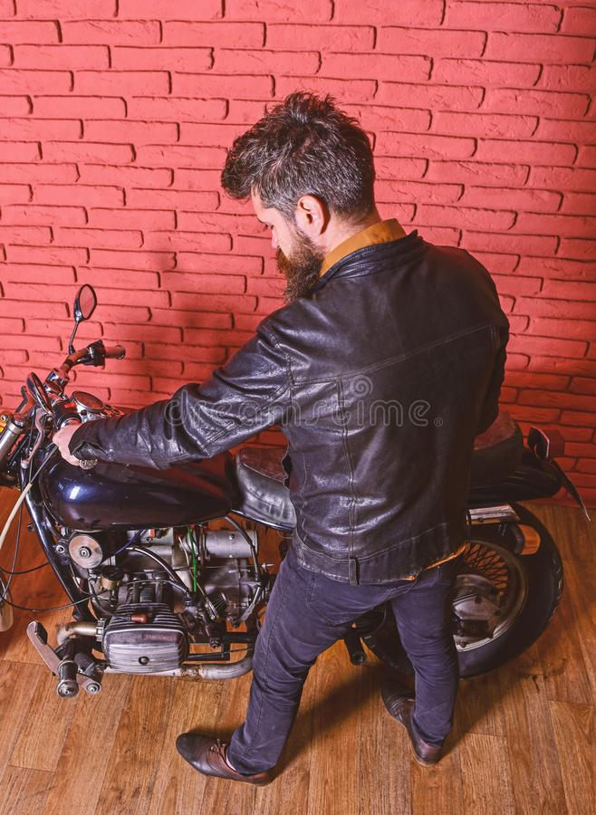 Hipster, brutal biker in leather jacket sits down on motorcycle, rear view. Man with beard, biker in leather jacket near. Motor bike in garage, brick wall royalty free stock photos