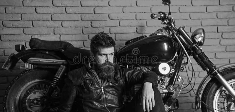 Hipster, brutal biker on pensive face in leather jacket sit on floor near motorcycle. Brutal biker concept. Man with. Beard, biker in leather jacket near motor stock images