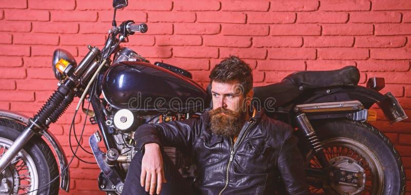 Hipster, brutal biker on pensive face in leather jacket sit on floor near motorcycle. Brutal biker concept. Man with. Beard, biker in leather jacket near motor stock image