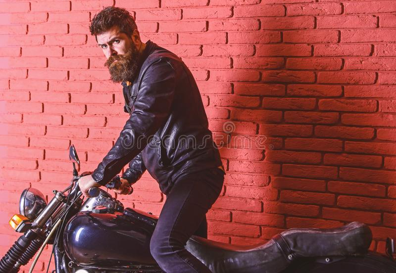 Hipster, brutal biker on serious face in leather jacket gets on motorcycle. Man with beard, biker in leather jacket near. Motor bike in garage, brick wall stock photos