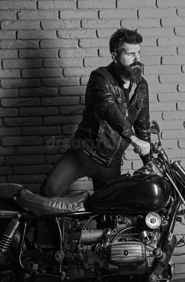 Hipster, brutal biker on serious face in leather jacket gets on motorcycle. Masculine passion concept. Man with beard. Biker in leather jacket near motor bike royalty free stock images