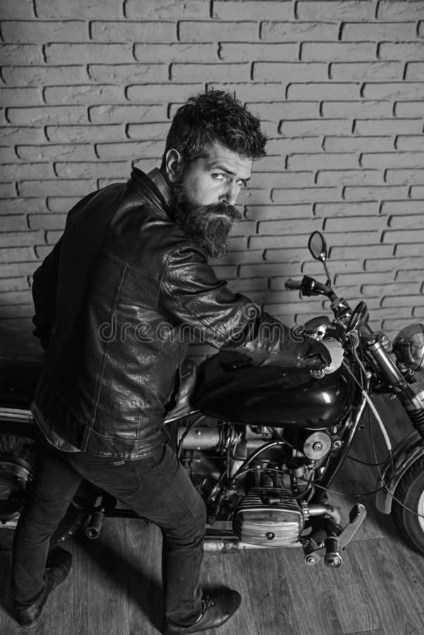 Hipster, brutal biker on strict face in leather jacket sits down on motorcycle. Man with beard, biker in leather jacket. Near motor bike in garage, brick wall royalty free stock image
