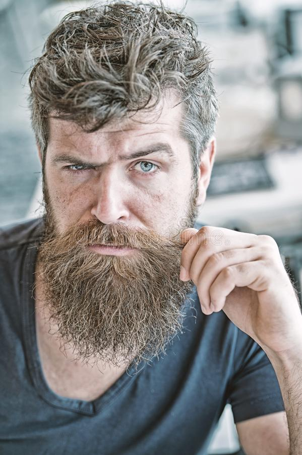 Hipster brutal guy twisting mustache. Man confident brutal bearded macho. Grooming and barber shop concept. Masculinity. And brutality. Male beauty. Macho royalty free stock image