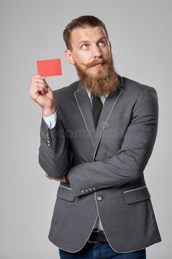 Hipster business man. With beard and mustashes in suit standing over grey background holding credit card looking up royalty free stock photography