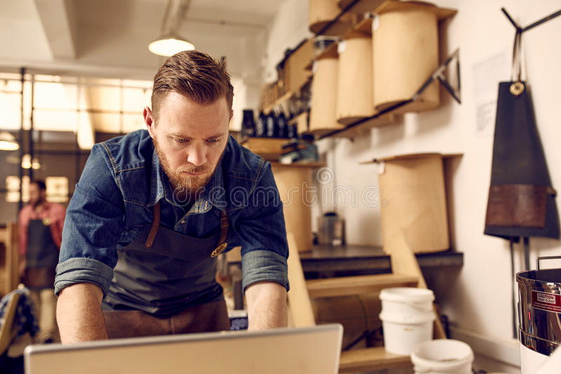 Hipster business owner working on laptop in his modern work. Handsome young business owner with a subtle hipster style working seriously on a lsptop with his stock photos