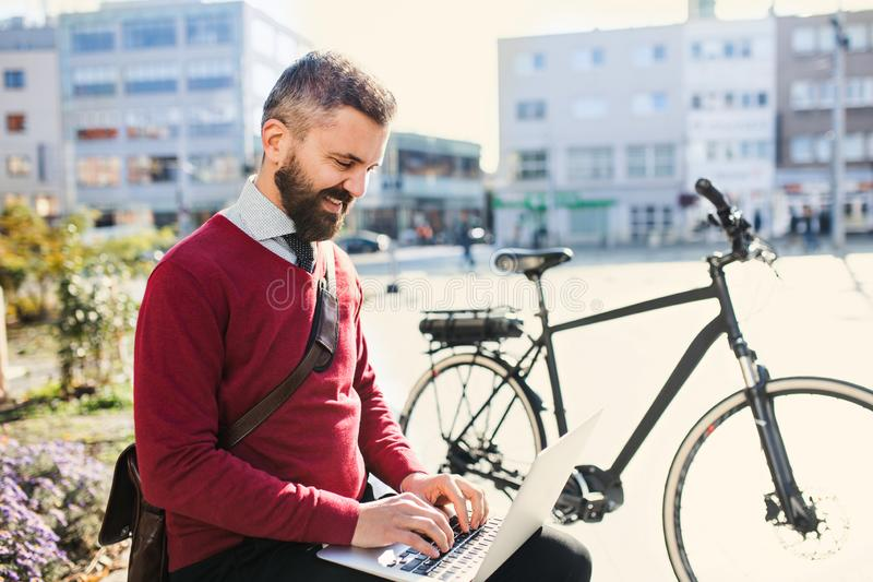 Hipster businessman commuter with bicycle on the way to work in city, using laptop. stock images