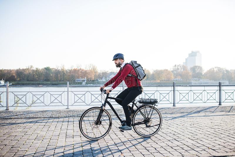 Hipster businessman commuter with electric bicycle traveling to work in city. royalty free stock images