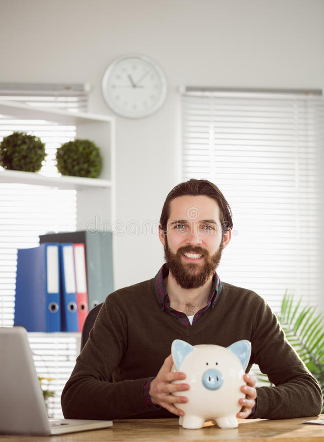 Hipster businessman with a piggy bank royalty free stock images
