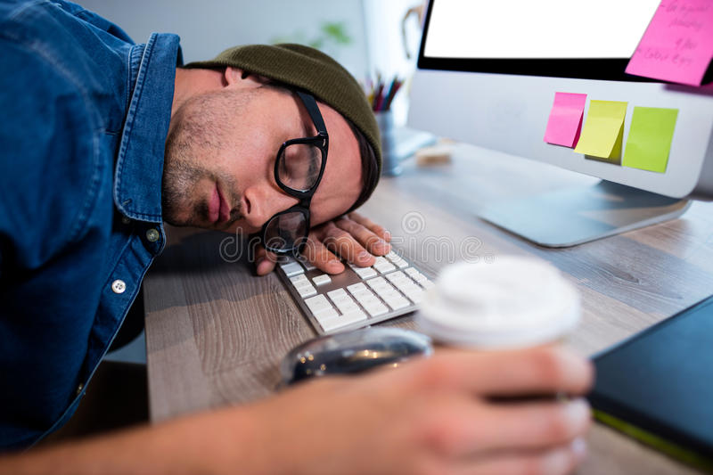 Hipster businessman sleeping at his desk. In modern office royalty free stock image
