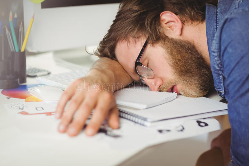 Hipster businessman sleeping at his desk. In his office stock photography