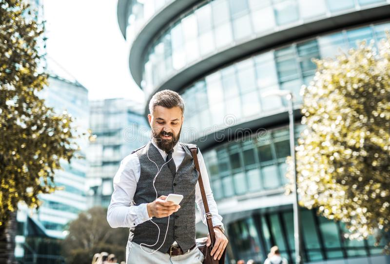 Hipster businessman with smartphone and earphones walking on the street. royalty free stock image