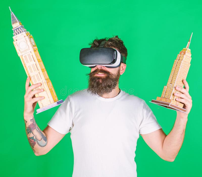 Hipster on busy face study architecture in virtual reality. VR education concept. Guy in VR glasses hold in hands Big. Ben and Empire State Building. Man with royalty free stock photography