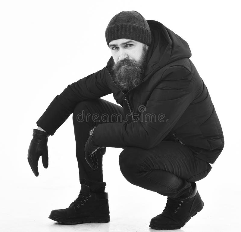 Hipster with calm face wears warm clothes, sits on haunches. stock photos