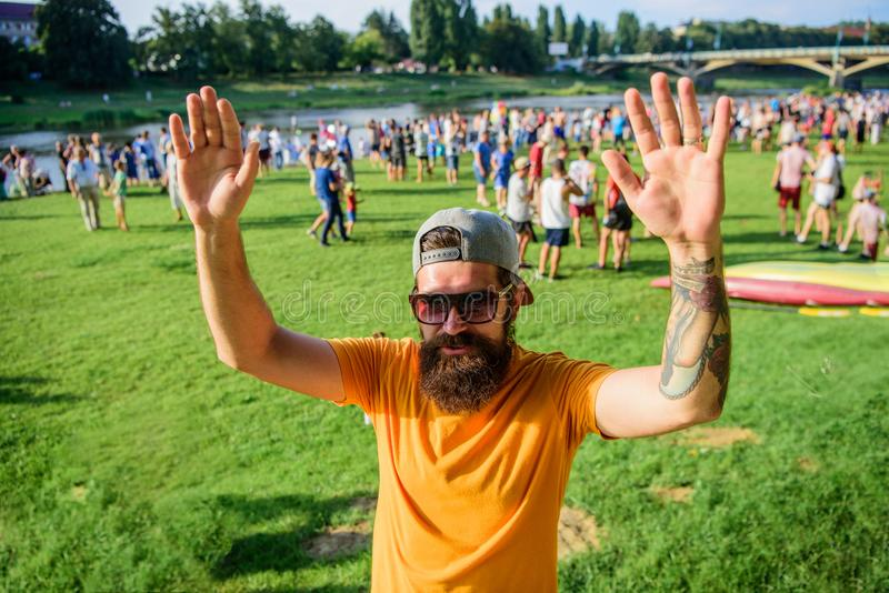 Hipster in cap happy to meet friend at event picnic fest or festival. Happy to meet you. Man bearded hipster in front of stock image