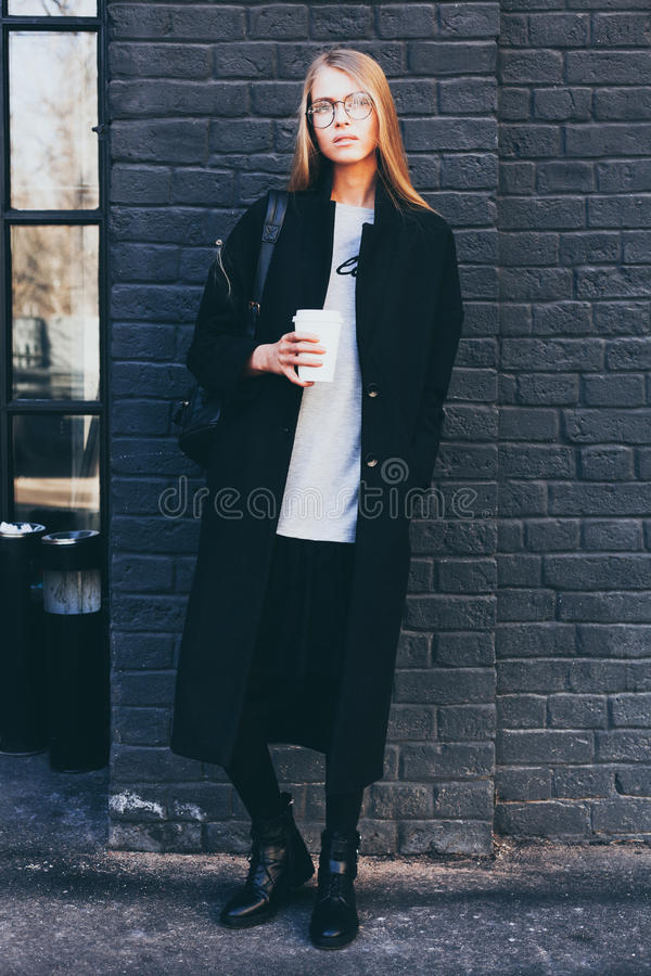 A hipster casual girl with long blond hair wearing a stylish coat and round glasses while standing on a black brick stock photos
