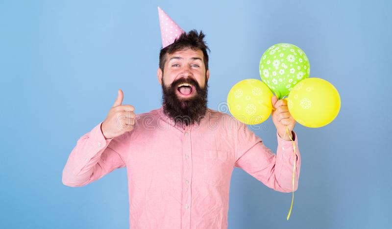 Hipster celebrates birthday, shows thumb up gesture. Birthday boy concept. Guy in party hat with air balloons celebrates stock images