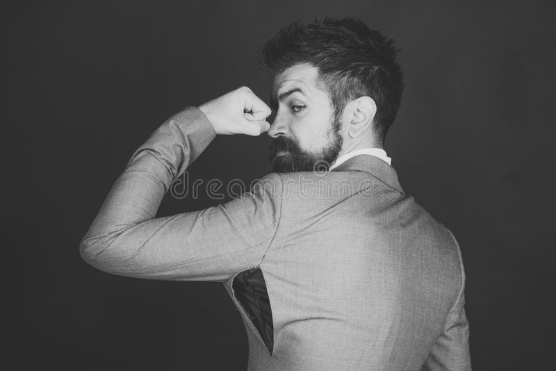Hipster chose small size jacket, seam torn under armpit. Guy posing in counterfeit or fake brand. Man with beard wears jacket with hole on dark background. Bad stock images