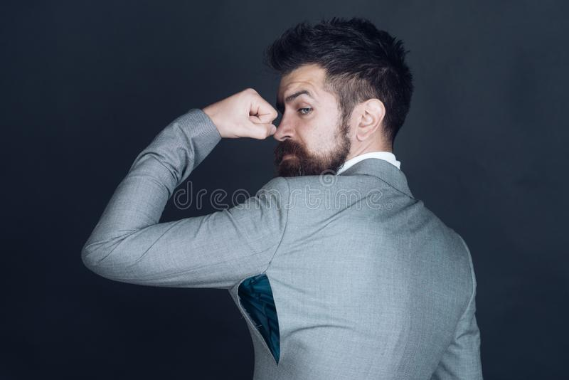 Hipster chose small size jacket, seam torn under armpit. Guy posing in counterfeit or fake brand. Man with beard wears jacket with hole on dark background. Bad royalty free stock photography