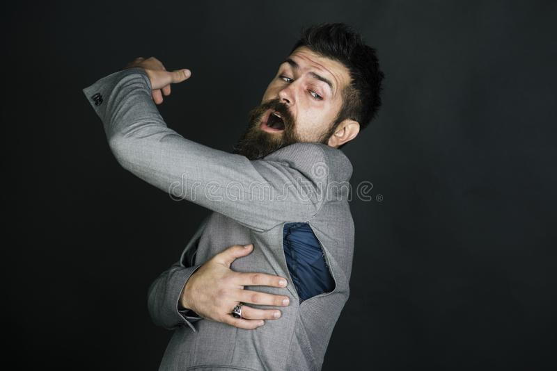 Hipster chose small size jacket, seam torn under armpit. Man with beard wears jacket with hole on dark background. Bad quality of clothes concept. Surprised stock photography