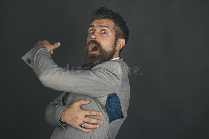 Hipster chose small size jacket, seam torn under armpit. Surprised guy bought counterfeit or fake brand. Man with beard wears jacket with hole on dark royalty free stock photo