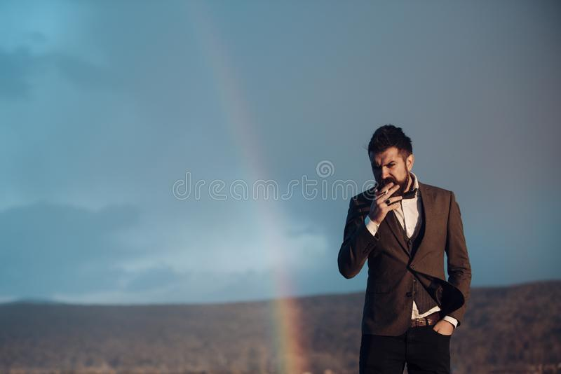 Hipster with cigarette and rainbow. Bearded man smoke on natural landscape. Fashion smoker on fresh air. Addiction and stock photography