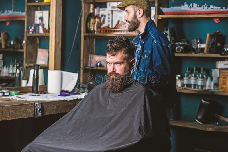 Hipster client getting haircut. Client with beard ready for trimming or grooming. Man with beard covered with black cape. Waiting while barber changing clipper royalty free stock image