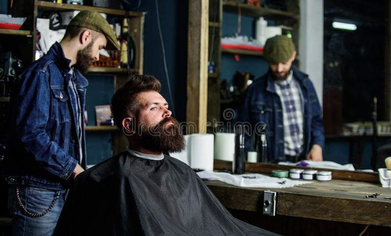 Hipster client getting haircut. Man with beard covered with black cape waiting while barber changing clipper grade. Client with beard ready for trimming or stock images