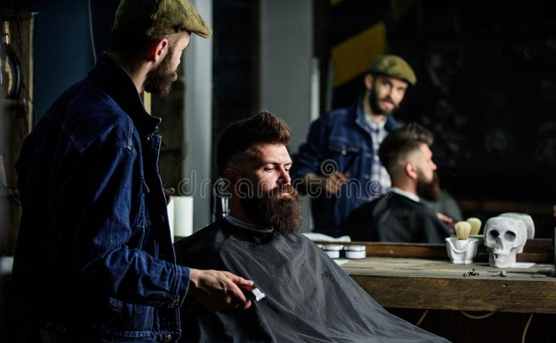 Hipster client got new haircut. Barber with hair clipper looking at mirror, barbershop background. Professional master royalty free stock image
