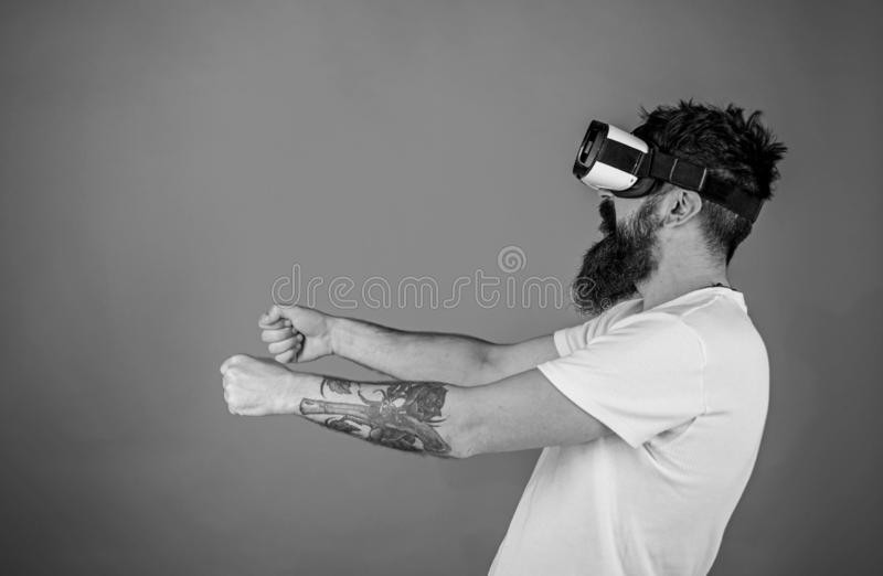 Hipster on concentrated face driving car on high speed in virtual reality. Man with beard in VR glasses driving car, red. Background. Virtual racing concept stock image