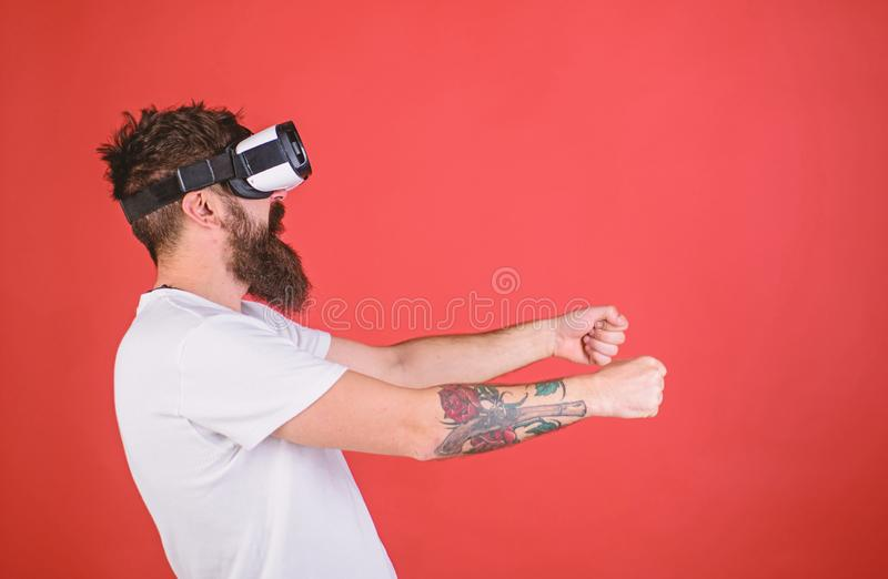 Hipster on concentrated face driving car on high speed in virtual reality. Man with beard in VR glasses driving car, red. Background. Virtual racing concept royalty free stock images