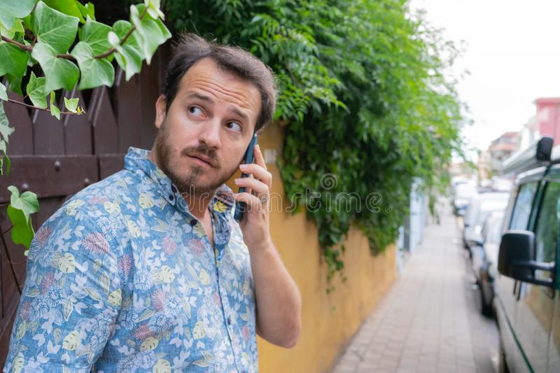Hipster confused and afraid looking away with serious expression in the street while talk with the smart phone. Dude with beard. Out distracted and surprised stock image