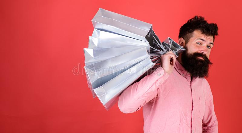 Hipster on cool face is shopping addicted or shopaholic. Guy shopping on sales season with discounts. Shopping concept. Man with beard and mustache carries stock photos