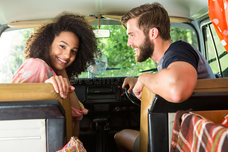 Hipster couple driving in camper van stock images