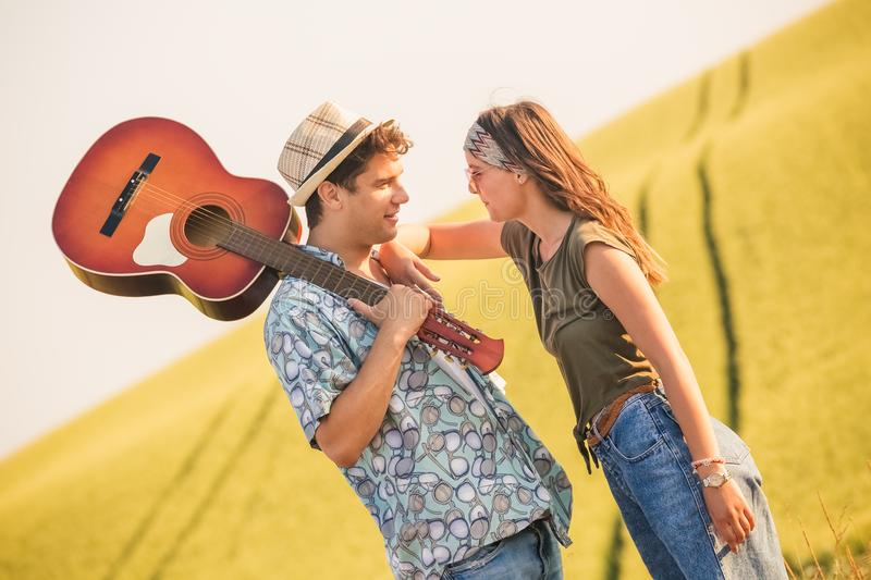 Hipster couple with guitar in the field. Young fashionable couple with acoustic guitar in nature stock photo