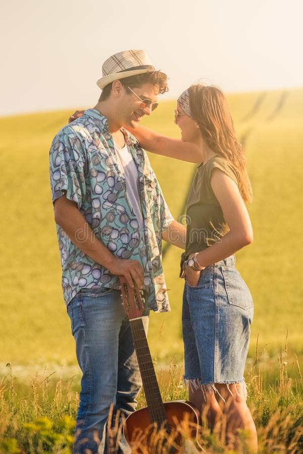 Hipster couple with guitar in the field. Young fashionable couple with acoustic guitar in nature royalty free stock photography