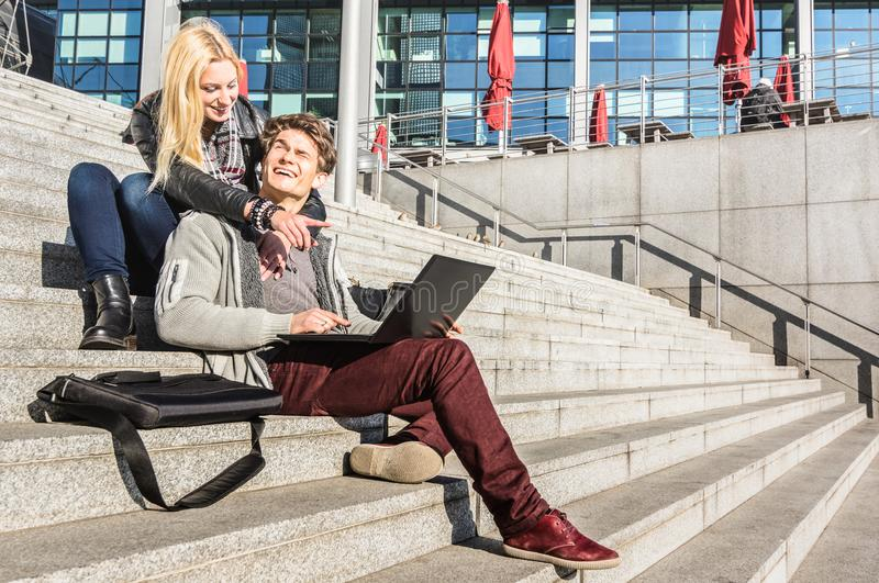 Hipster couple having fun using computer laptop in urban location royalty free stock image