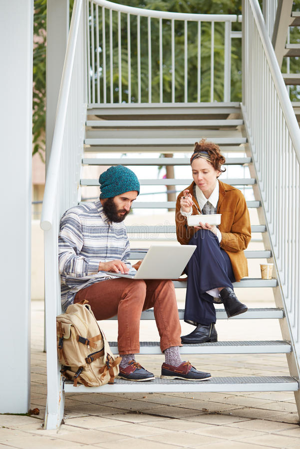 Hipster couple using computer and eating lunch outdoors royalty free stock images