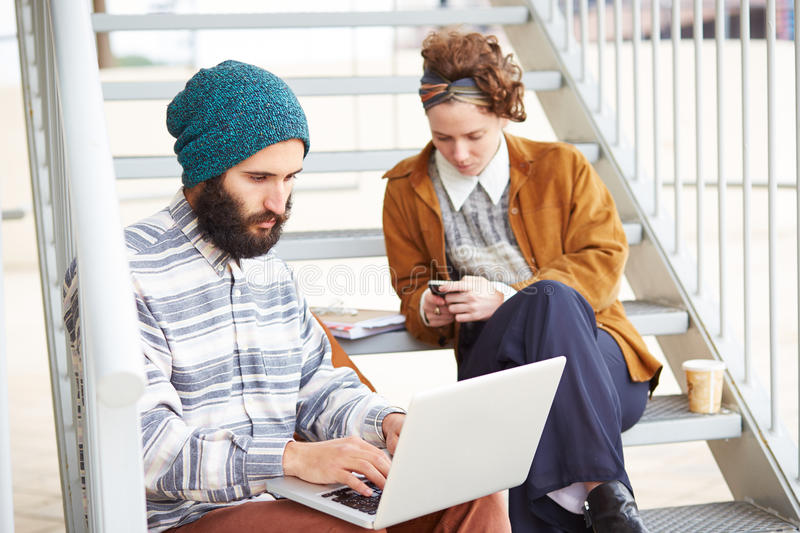 Hipster couple using computer and smartphone outdoors stock image