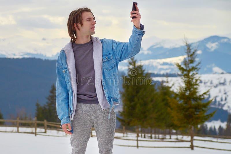 hipster die op zoek is naar een mobiel signaal in de bergen stock fotografie
