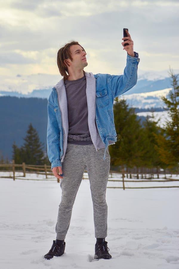 hipster die op zoek is naar een mobiel signaal in de bergen stock afbeeldingen