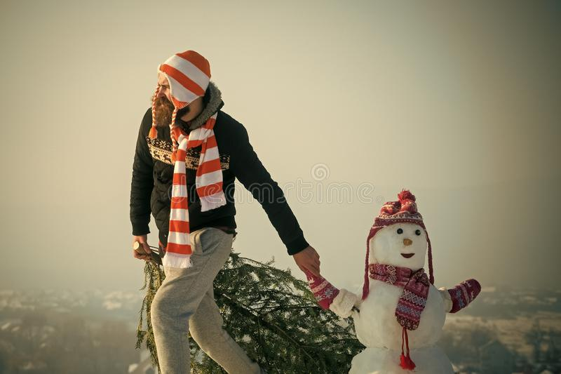 Hipster dragging xmas tree on snowy winter landscape. Man and snowman walking on blue sky. Holiday celebration concept. Christmas and new year. Guy and snow stock image