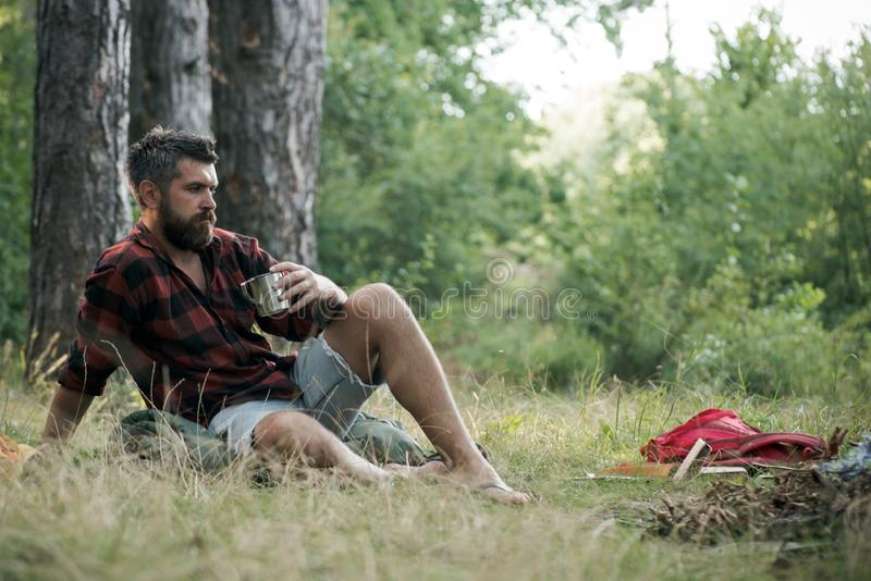 Hipster drink tea or coffee at bonfire. Bearded man relax with mug at campfire. Guy enjoy camping in forest. Summer royalty free stock photography