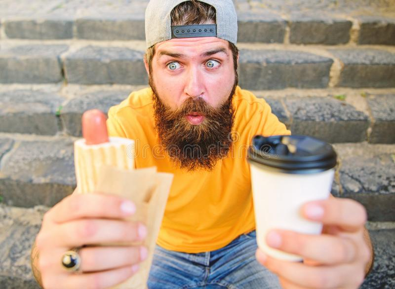 Hipster eat hot dog drink coffee. Hipster enjoy hot dog drink paper cup. Fast food for lunch common idea. Nutritional. Issues concerning street food. Man royalty free stock photo