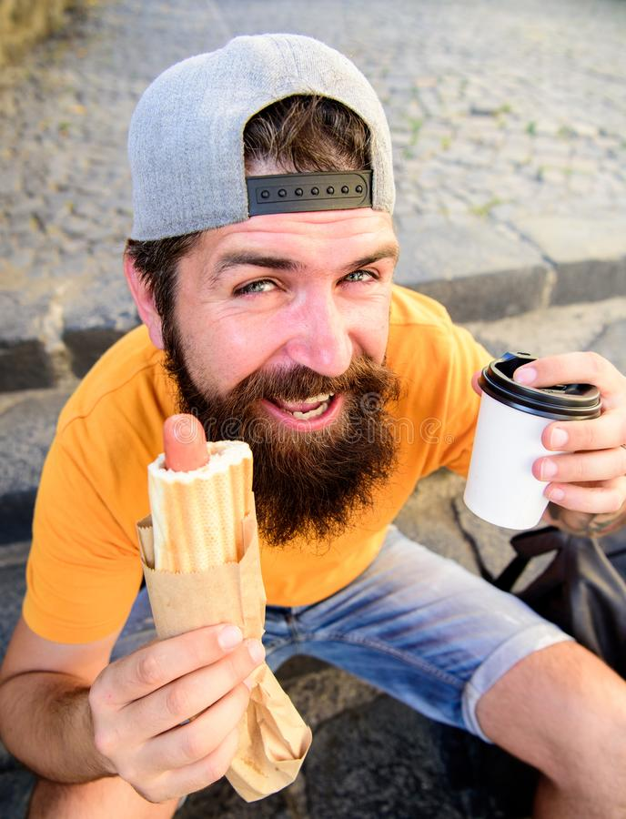 Hipster eat hot dog while sit on stairs outdoors. Hipster enjoy hot dog and drink paper cup. Man bearded enjoy street royalty free stock image