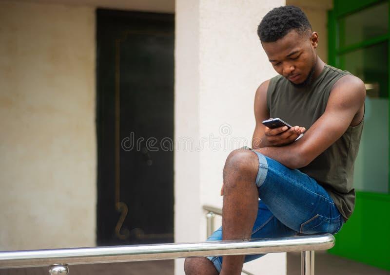 Hipster en ung man som använder en smartphone Afrikansk amerikantonåring som rymmer ett mobilt smartphonesammanträde på räcket royaltyfria bilder