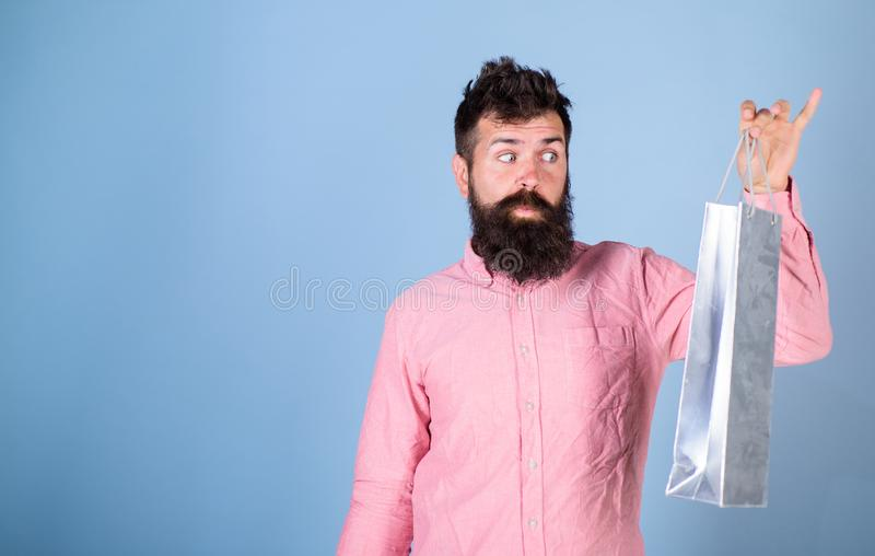 Hipster on excited face shopping addicted or shopaholic. Guy shopping on sales season with discounts. Man with beard. Look at shopping bag, light blue royalty free stock images